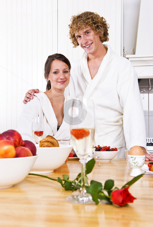 Valentine breakfast stock photo, Young couple at a valentine's breakfast at the counter in a cosy kitchen by Corepics VOF
