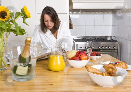 Champagne breakfast stock photo, Young woman enjoying the morning paper during a cosy champagne breakfast by Corepics VOF