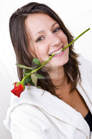 Woman biting rose stock photo, Young pretty brunette biting a red rose by Corepics VOF