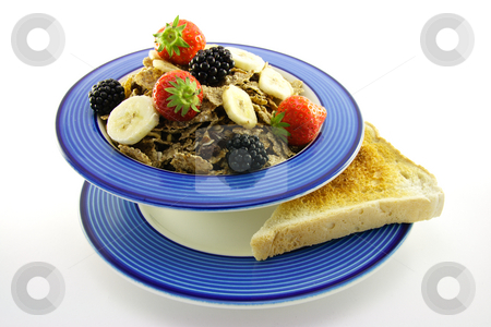 Bran Flakes in a Blue Bowl stock photo, Crunchy looking delicious bran flakes and juicy fruit in a blue bowl with toast on a white background by Keith Wilson