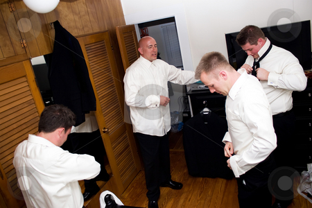 Groomsmen Getting Ready stock photo, A groom along with his three groomsmen getting dressed and ready for the wedding. by Todd Arena