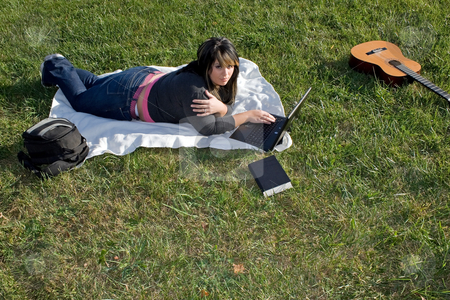 Woman Using a Laptop stock photo, A young woman laying in the grass and using her laptop computer.  She could be a college student or even a musician. by Todd Arena