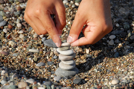 Rocks stack stock photo, Child hands building a rocks stack carefully by Julija Sapic