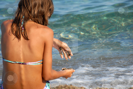 Girl on seashore stock photo, Young girl long brown hair sitting on beach playing with rocks by Julija Sapic