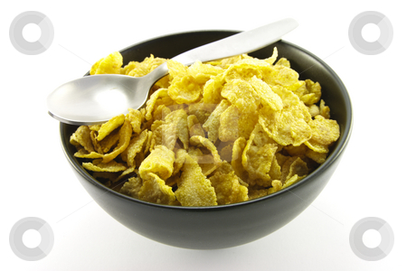 Cornflakes in a Bowl stock photo, Golden cornflakes in a bowl with a spoon on a white background by Keith Wilson