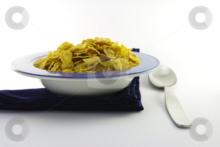 Cornflakes in a Blue Bowl with a Spoon stock photo, Golden crisp cornflakes in a round blue bowl with a black napkin and a spoon on a white background by Keith Wilson