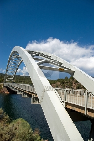 Bridge with Storm stock photo, An arched highway bridge spanning a small lake with a storm in the sky. by Andrew Orlemann