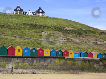 Beach huts and house stock photo, Colourful beach huts at the coast with a house on a hill by Mike Smith