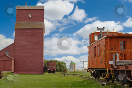 Grain Elevator With Train stock photo, A grain elevator looming in the distance with a rear of a train sitting close by by Richard Nelson