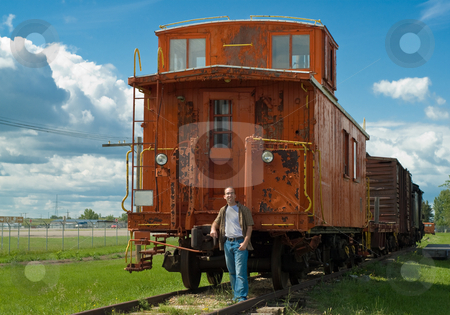 Train Caboose stock photo, A train caboose shot on a partly cloudy day along with a young man to show the size of it by Richard Nelson