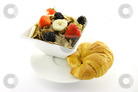Bran Flakes in a White Bowl stock photo, Crunchy looking delicious bran flakes and juicy fruit in a white bowl with a croissant on a white background by Keith Wilson