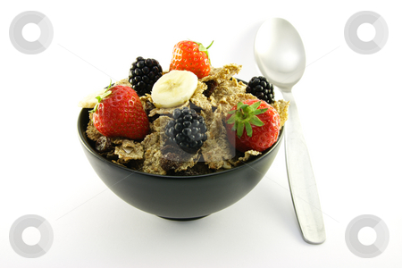 Bran Flakes in a Black Bowl stock photo, Delicious crunchy looking bran flakes and juicy fruit in a black bowl with a spoon on a white background by Keith Wilson
