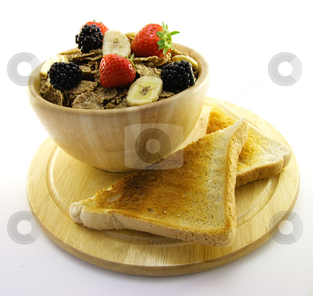 Bran Flakes in a Wooden Bowl stock photo, Crunchy looking delicious bran flakes and juicy fruit in a wooden bowl with toast on a white background by Keith Wilson