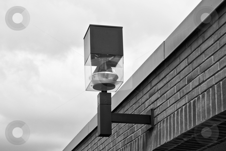 Industrial light fixture attached to a brick wall. stock photo, An industrial looking light fixture attached a brick wall with a view of the roof.  This image is shot in black and white. by Joseph Jenkins