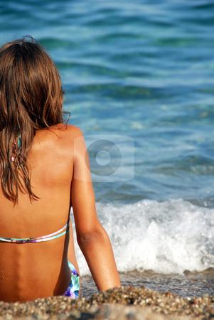 Girl on seashore stock photo, Young girl long brown hair sitting on beach by Julija Sapic