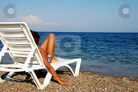 Girl on beach stock photo, Young girl lying in chair on beach looking at sea view by Julija Sapic