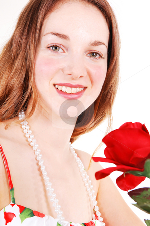 Beautiful woman with red, rose. stock photo, A very pretty young girl in an red rose dress and gorgeous long red hair standing und holding a red rose to her face, on white background. by Horst Petzold