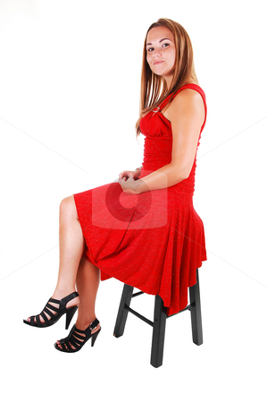 Woman sitting on chair. stock photo, Lovely young woman in high heels and beautiful red dress sitting on a bar chair in the studio with long brown hair. On white background. by Horst Petzold