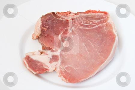 Pork chop stock photo, Fresh raw pork chop on a white plate by ANTONIO SCARPI