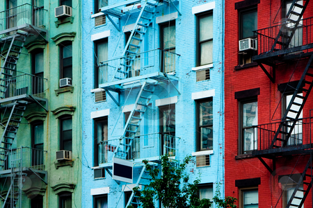 Colorful apartment buildings with fire escapes stock photo, Three colorful, red, blue and green, apartment buildings facades with emergency escapes. Typical New York City, Boston  or Chicago rental complexes with fire escape stairs next to the windows. by Paul Hakimata