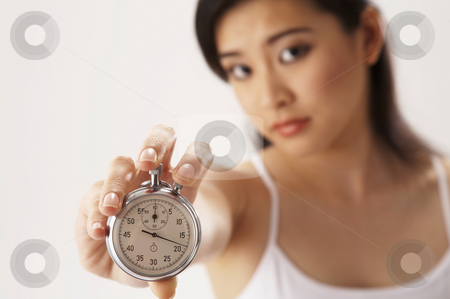Woman  holding watch stock photo, Young woman holding a stop watch by eskaylim