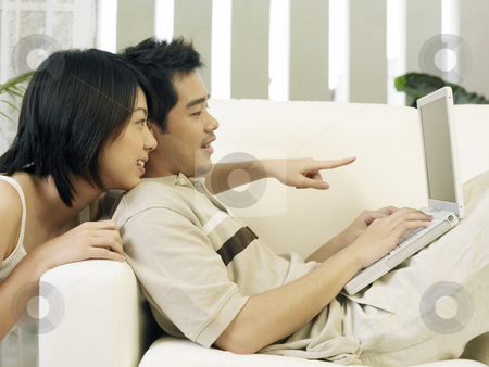 Asian couple at home stock photo, A couple is surfing the internet together by eskaylim