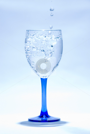 Water drop into glass stock photo, Water drop into glass on blue background by Lawren