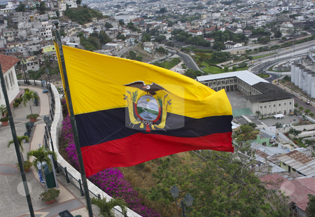 Ecuadorian woven bags stock photo, An Ecuadorian flag with yellow, blue and red strips flying over a city in Ecuador, South America by Sharron Schiefelbein