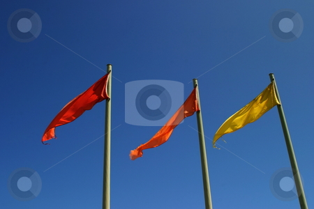 Color Flags stock photo, Three red, orange and yellow flag with blue sky in the background by Henrik Lehnerer
