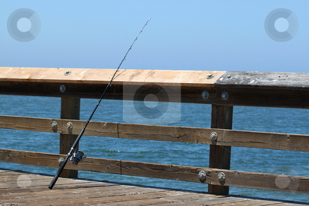 Fishing Rod stock photo, Fishing rod standing at a pier with the ocean in the background. by Henrik Lehnerer