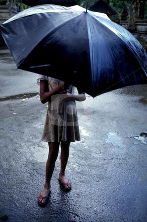Girl under Umbrella stock photo, Indonesia, Bali, Girl in Rain by David Ryan