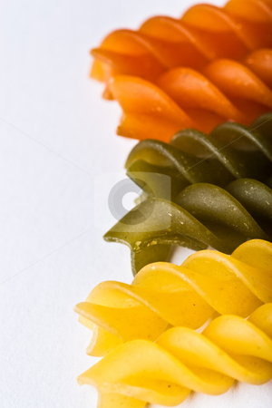 Pasta stock photo, Macro of colorful raw fusilli or rotini pasta in studio by Jose Wilson Araujo