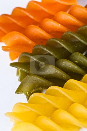 Pasta stock photo, Macro of colored raw fusilli or rotini pasta in studio by Jose Wilson Araujo