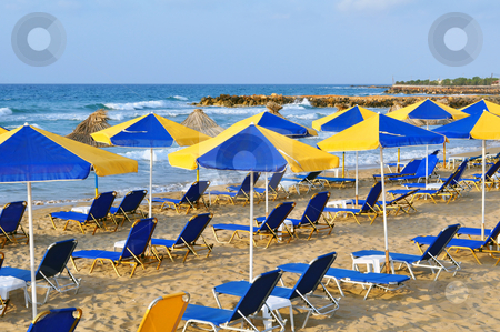 Sunbeds and beach umbrellas stock photo, Travel photography: summer: sunbeds and umbrellas in mediterranean beach by Fernando Barozza