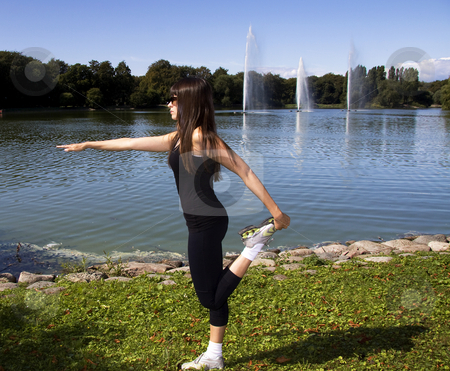 Woman stretching her legs stock photo, Latina is working out in the park stretching before a run by Daniel Kafer