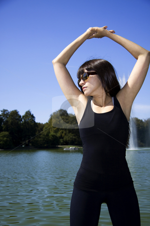 Woman doing yoga stock photo, Latina is working out in the park stretching before a run by Daniel Kafer