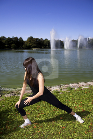 Woman stretching in the park stock photo, Latina is working out in the park stretching before a run by Daniel Kafer