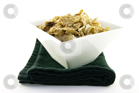 Bran Flakes in a White Bowl stock photo, Crunchy delicious looking bran flakes in a white bowl and a black napkin on a white background by Keith Wilson