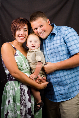 Happy Young Family stock photo, A studio portrait of a happy young family. by Travis Manley