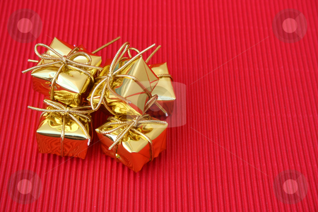 Many Gifts stock photo, Small golden christmas gifts on a red background by Vanessa Van Rensburg