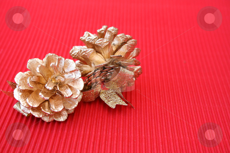 Pine Cones stock photo, Golden decorated pine cones on a red background by Vanessa Van Rensburg