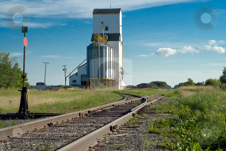 Prairie Railroad Tracks stock photo, Prairie railroad tracks running along beside a tall grain elevator and vanishing in the distance by Richard Nelson
