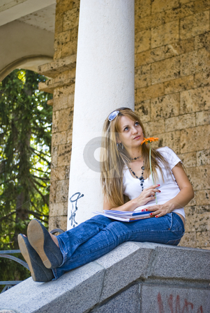 Beautiful young woman with books and flower stock photo, Beautiful young woman with books and flower outdoor by Desislava Dimitrova