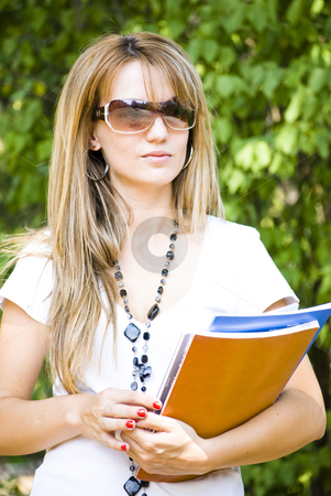 Young beautiful woman holding books stock photo, Young beautiful woman holding books walking in park by Desislava Dimitrova