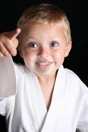 Karate Boy stock photo, Young boy wearing his karate uniform on a black background by Vanessa Van Rensburg