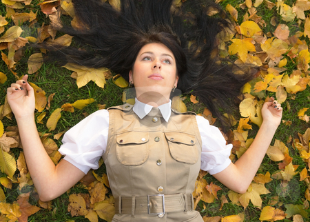 Lying on golden leaves stock photo, Pretty brunette girl resting in an autumn park by Mikhail Lavrenov
