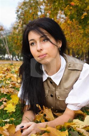 Brunette girl and golden leaves stock photo, Pretty brunette girl resting in an autumn park by Mikhail Lavrenov