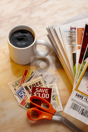 Clipping coupons stock photo, Savings coupons, newspapers, a pair of scissors and a cup of coffee shot on marble table by James Barber