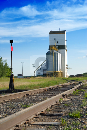 Grain Elevator stock photo, A large grain elevator in the prairies is situated near some empty railroad tracks, shot with a nice blue sky by Richard Nelson