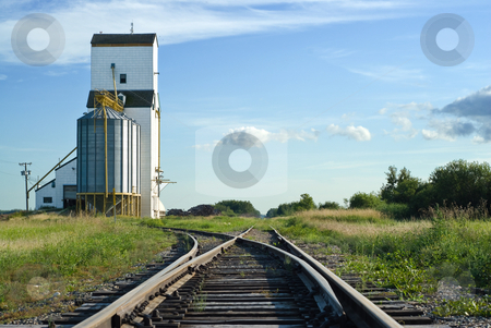 Crossroads stock photo, A crossroad section of the railroad tracks with one side going to a grain elevator and the other going straight and disappearing in the distance by Richard Nelson